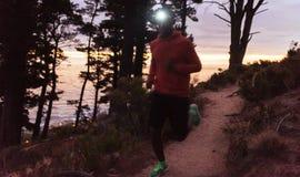 佩带前灯的年轻非洲人跑步在黄昏 库存图片