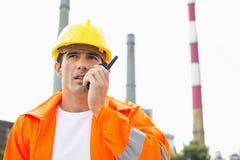 佩带反射性工作服的男性建筑工人沟通在携带无线电话在站点 免版税库存照片