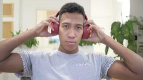 佩带听的音乐的非洲人红色耳机 影视素材