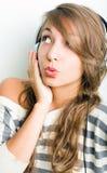 佩带吹哨的年轻人的美丽的女孩耳机 库存照片
