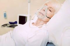 佩带呼吸支持的可怜的资深夫人在医院 库存照片