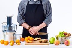 佩带围裙的匿名人,准备新鲜水果汁使用现代电榨汁器,在白色的健康生活方式戒毒所概念 免版税图库摄影