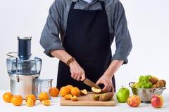佩带围裙的匿名人,准备新鲜水果汁使用现代电榨汁器,在白色的健康生活方式戒毒所概念 免版税库存照片
