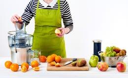 佩带围裙的匿名妇女,准备新鲜水果汁使用现代电榨汁器,健康生活方式戒毒所概念 库存图片