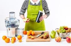 佩带围裙的匿名妇女,准备新鲜水果汁使用现代电榨汁器,健康生活方式戒毒所概念 图库摄影