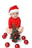 佩带圣诞老人帽子和圣诞树的女婴 免版税库存图片