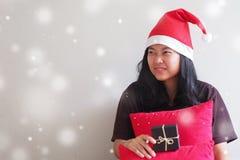 佩带圣诞老人帽子和坐的年轻女人 免版税库存图片
