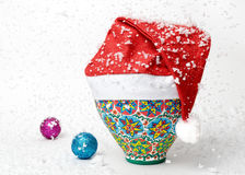 佩带圣诞老人帽子和落的雪的埃及五颜六色的瓦器花瓶 图库摄影