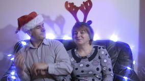 佩带圣诞老人帽子和驯鹿垫铁的中年夫妇坐长沙发和跳舞 影视素材