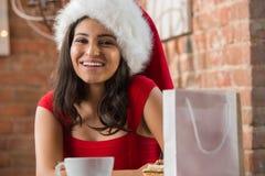 佩带圣诞老人帽子开头圣诞节礼物的迷人的妇女 库存图片