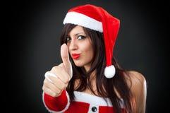 佩带圣诞老人的女孩给产生一个好的符号穿衣 库存图片