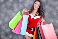 佩带圣诞老人的性感的女孩穿衣与颜色袋子 库存照片