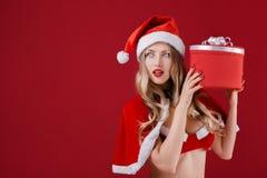 佩带圣诞老人的性感的妇女穿衣与圣诞节礼物 免版税库存照片