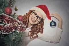 戴佩带圣诞老人的眼镜的画象美丽的年轻圣诞节女孩穿衣 免版税图库摄影