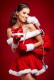 佩带圣诞老人的美丽的性感的女孩穿衣与圣诞节g 免版税库存照片