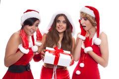 佩带圣诞老人的美丽的性感的女孩穿衣与当前bo 免版税图库摄影