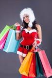 佩带圣诞老人的美丽的性感的女孩穿衣与颜色袋子 免版税图库摄影