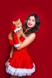 佩带圣诞老人的美丽的性感的女孩画象穿衣与红色英国猫 免版税库存照片