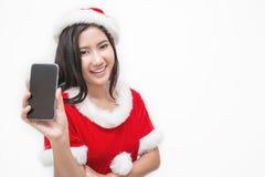 佩带圣诞老人custume用她的手的亚裔美丽的妇女画象举行MOBIL响度单位 免版税库存照片