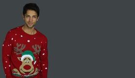 佩带圣诞节套头衫的英俊的人 免版税图库摄影