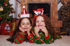 佩带圣诞节的两个美丽的微笑的litle女孩给放置在一张白色地毯穿衣,有室内chimmey背景 库存照片