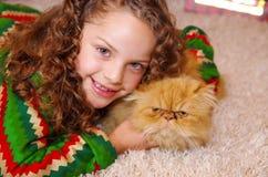佩带圣诞节的美丽的微笑的litle女孩穿衣,拥抱她的黄色猫,放置在一张白色地毯 免版税库存图片