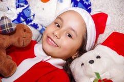 佩带圣诞节的美丽的微笑的litle女孩穿衣,拥抱麋和熊女用连杉衬裤,放置在一条白色毯子 图库摄影