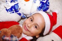 佩带圣诞节的美丽的微笑的litle女孩穿衣,拥抱麋和熊女用连杉衬裤,放置在一条白色毯子 库存图片