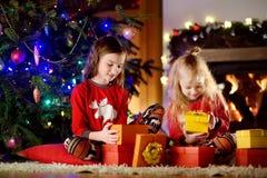 佩带圣诞节睡衣的愉快的妹使用由一个壁炉在自圣诞前夕的一个舒适黑暗的客厅 库存照片