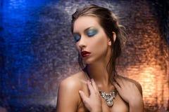 佩带在一五颜六色的箔backgr的美丽的女孩一条项链 免版税图库摄影