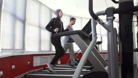 佩带在一台连续模拟器和一个人的运动员妇女一hijab健身房的 影视素材