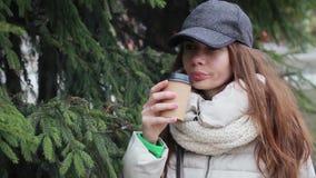 佩带在从一一次性杯的一份灰色盖帽和白色外套饮用的咖啡的美丽的女孩 在背景的云杉的树 股票录像
