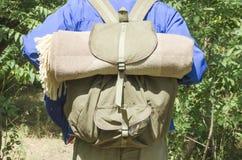 佩带在他的肩膀的旅行家一个背包在一次旅途期间在森林里 免版税库存图片