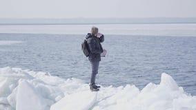 佩带在冰川的人一个温暖的外套身分调直他的头发和看  令人惊讶的本质的多雪 股票视频