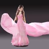 佩带在吹的美丽的深色的女孩桃红色礼服隔绝了o 免版税图库摄影