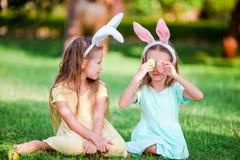 佩带在复活节的两个小女孩兔宝宝耳朵户外 免版税库存图片