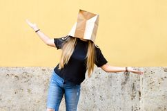 佩带在她的头的妇女一个纸袋 图库摄影