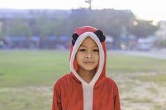 佩带在学校草坪的亚洲男孩红色圣诞节背景 免版税库存照片