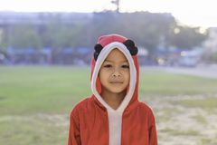佩带在学校草坪的亚洲男孩红色圣诞节背景 库存照片