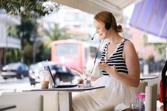 佩带在室外咖啡馆的笑的妇女一个耳机 免版税库存照片