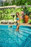 佩带在室外水池的妇女蓝色比基尼泳装逗留在手段 免版税库存照片
