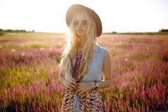 佩带在帽子和圆的太阳镜的快乐的白肤金发的女孩,供以座位在一个花卉领域,在美好的日落背景后 免版税图库摄影