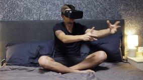 佩带在床上的人VR耳机 看,微笑和波浪用手 手表VR录影 影视素材
