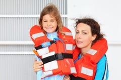 佩带在救生衣的微笑的母亲和女儿 库存照片