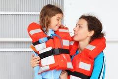 佩带在救生衣的母亲和女儿 图库摄影