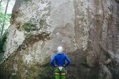 佩带在有准备的绳索的上升的设备的年轻人站立在一个石岩石前面和上升 图库摄影