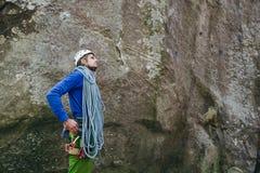 佩带在有准备的绳索的上升的设备的年轻人站立在一个石岩石前面和上升 免版税库存照片