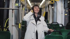 佩带在有听音乐和滑稽的跳舞的耳机的外套的年轻女人画象在公共交通工具 ? 影视素材