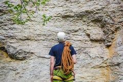 佩带在有站立在一个石岩石前面的绳索的上升的设备的年轻人 免版税图库摄影