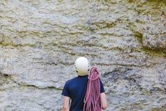 佩带在有站立在一个石岩石前面的绳索的上升的设备的年轻人 库存照片